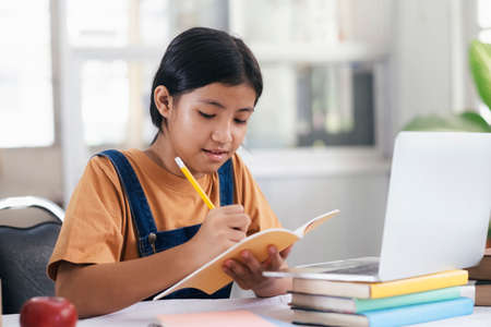 Happy asian girl learning online at home. Education and e-learning concept.