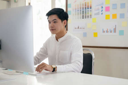 Young finance market analyst working at office and analyze online marketing in his computer.