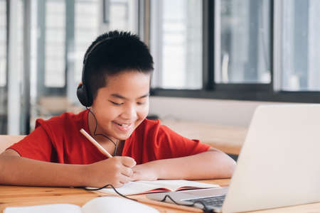Cheerful child excited using computer for online learining. Online education and self study and homeschooling concept. Stock Photo