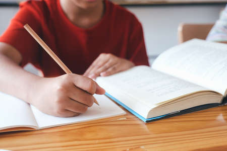 Elementary school pupil is self studying and doing homework at home. Education and distance learning for kids. Homeschooling during quarantine. Stock Photo