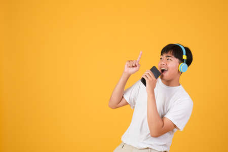 Happy young man singing while using earphones and mobile phone isolated over yellow background.