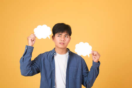 Asian man holding speech bubble with empty space for text on yellow background.