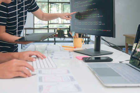 Programmer and UX UI designer working in a software development and coding technologies. Mobile and website design and programing development technology. Stock Photo