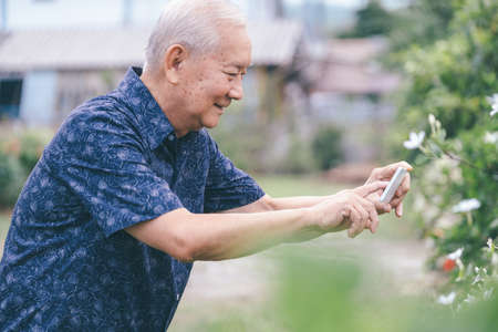 Happy asian senior man in the graden taking a picture with mobile phone. Happy retirement life. Stock Photo
