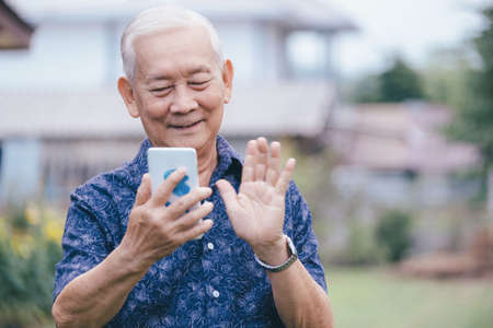 Happy asian elder man using smartphone. Pleasant 80s grandfather typing message for grown up kids in mobile app, watching photos.