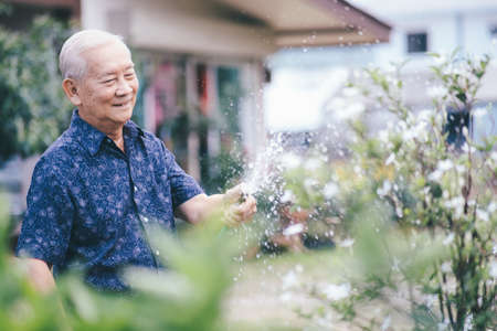 Happy asian senior man in his garden. Happy retirement age. Stock Photo