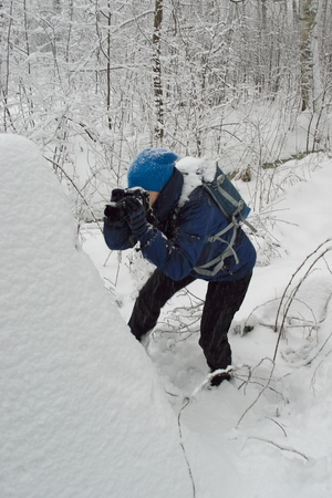 winter scenery image with view to Unidentifiable young adult woman in blue colored hiker outfit doing photography at the strain covered with snow