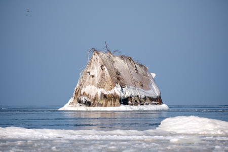 Tranquil wintertime scene with stranded ship's bow above the waterline and frozen in ice coastline in foreground at Mangalsala, Riga, Latvia. Horizontal image of the abandoned concrete shipwreck.