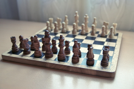 Horizontal close-up side view photographic image of a retro style wooden material chessboard with chess pieces set ready for strategic mind game. Dark brown colored figures in front.