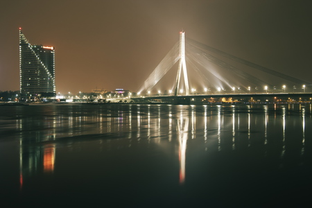 Riga, Latvia - February 5, 2017. Gorgeous long exposure panoramic view over the river Daugava to the brightly illuminated office building Saules Akmens and cable-stayed bridge Vansu Editorial