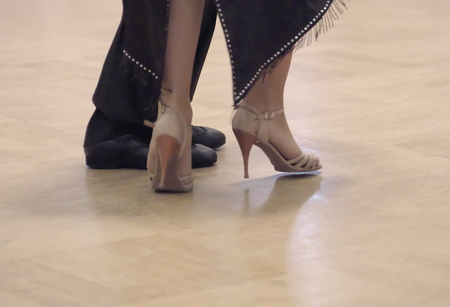 Horizontal close-up of a two unidentifiable dancer's shoes, feats and legs as they do the Argentine tango on dance floor during dance academy competition. Action shot of the professional dancers tangoing.