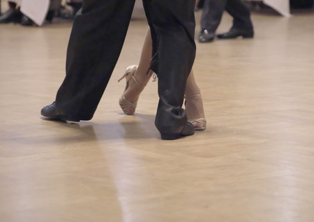 Horizontal close-up of a two unidentifiable dancers shoes, feats and legs as they do the Argentine tango on dance floor during dance academy competition. Action shot of the professional dancers tango