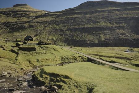 Picturesque landscape of historic outdoor museum King's farm Dúvugarðar in idyllic village Saksun on Island Streymoy of the Faroe islands. Layer-cake mountains in background. Glorious sceneries of the Faroes. Postcard motif. Stok Fotoğraf