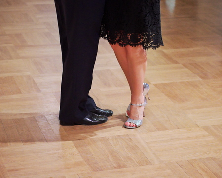 Close-up of a two unidentifiable dancers shoes, feats and legs as they do the Argentine tango on dance floor during dance academy competition. Action shot of the professional dancers tangoing.