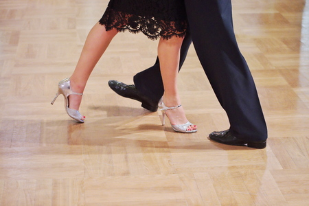 Close-up of a two unidentifiable dancer's shoes, feats and legs as they do the Argentine tango on dance floor during dance academy competition. Action shot of the professional dancers tangoing. 写真素材 - 123551963