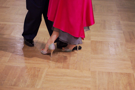 Close-up of a two unidentifiable dancer's shoes, feats and legs as they do the Argentine tango on dance floor during dance academy competition. Action shot of the professional dancers tangoing.