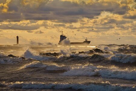 dramatic view to vessel leaving a harbor and passing lighthouse and pier, breaking through stormy waves, brightly lit by the sunset light Stockfoto