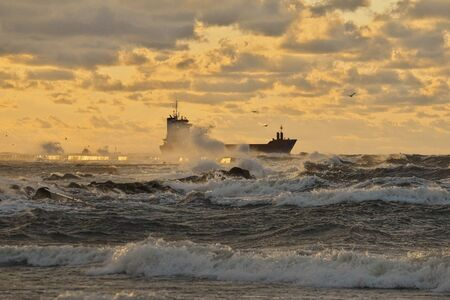 dramatic view to vessel leaving a harbor and passing a pier, breaking through stormy waves, brightly lit by the sunset light