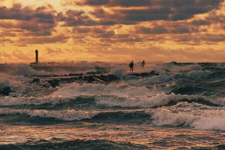 Two unrecognizable kite surfer running around the pier in the stormy sea lit by the sunset light under dramatic orange evening clouds, with a silhouette of lighthouse in the background
