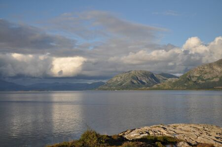 View to the sea and Vega archipelago mountains from the foot of the mountain Torghatten in Torget island in Brønnøy Municipality in Nordland county, Norway on sunny summer evening