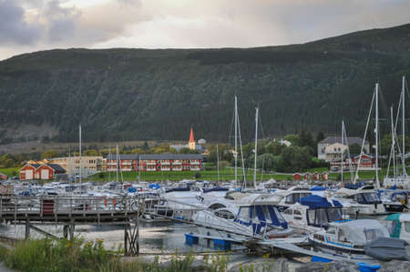 Nesna, Nordland/Norway - August 9 2016: View to the boats in Nesna port, Norway, with Nesna town in the background in sunset light, in cloudy summer evening Banco de Imagens - 157894669