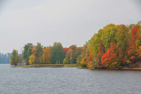 View to Perse river in Koknese in autumn with colorful red and yellow trees on the other river bank. Banco de Imagens
