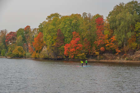View to Perse river in Koknese in autumn with colorful red and yellow trees on the other river bank. Two unrecognizable girls paddling on the sup in the river