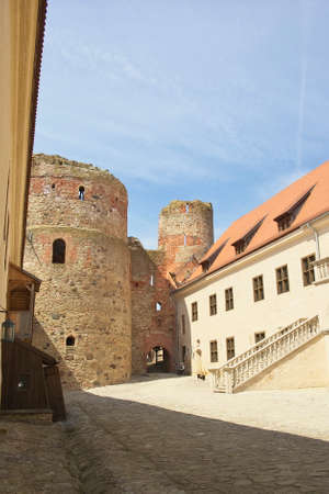 Horizontal image of the Bauska Castle yard with blue sky in background on bright a summer day