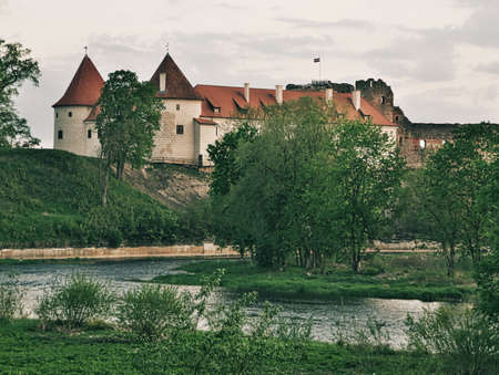 View to the Bauska Castle  with the river Memele in foreground on bright a summer day in Bauska, Latvia Banco de Imagens - 161368946