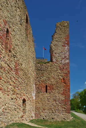 View to the red bricks ruins of Bauska Castle with the flag of Latvia on top on bright a summer day in Bauska, Latvia