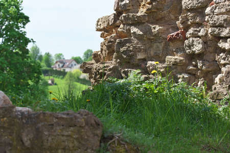 View to distant living building with the fragment of  ruins of Bauska Castle in foreground on bright summer day