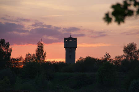 View to the water tower made from bricks with beautiful summer sunset in background in Bauska, Latvia