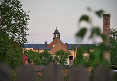 View to the distant tower with glass windows and wooden fence in foreground in evening light on summer night in Bauska,  Latvia Banco de Imagens - 162123245