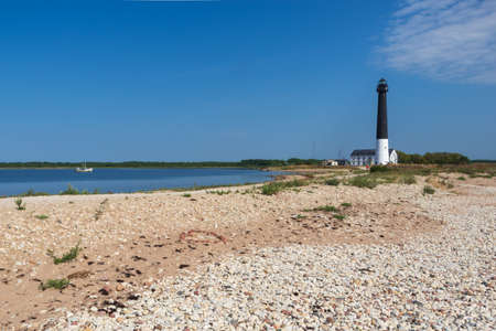View to the Sõrve lighthouse in Saaremaa island, Estonia. Beach with sand and pebbles in the foreground. Focus on heart made from red pebbles on the sand in the foreground