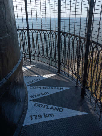 View to the signs on the floor on top of the building of historical Sõrve lighthouse showing the distance to Rostock, Copenhagen and Gotland.  Baltic sea in the background. Banco de Imagens