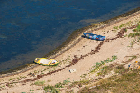 Aerial view to the two old boats - yellow and blue lying on the sea shore pebbles