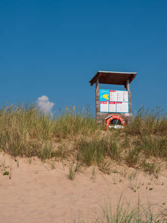 Information desk with lifebuoy on the sandy beach on Harilaid peninsula on bright sunny day