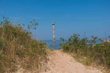 Path through the sandy dunes to the abandoned skew Kiipsaare lighthouse in Baltic sea on the NW Coast of Saaremaa Island on the Harilaid peninsula on bright sunny day. Focus on sand in foreground