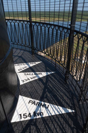 View to the signs on the floor on top of the building of historical Sõrve lighthouse showing the distance to Tallinn and Pärnu.  Baltic sea in the background. Banco de Imagens