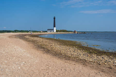 View to the beach of Sõrve peninsula cape with sand and pebbles by coastline. Lighthouse in the background.