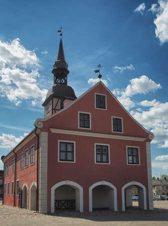 View to the Bauska town hall in historical centre with blue sky and white clouds in background in Bauska, Latvia. Banco de Imagens - 162153602