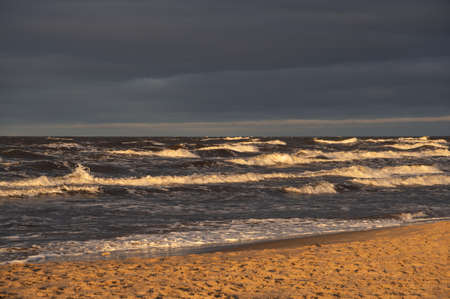 Wavy water of the Baltic sea and sandy shore in the warm evening sunlight.