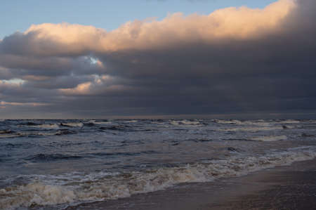 Wavy water of the Baltic sea and cloudy sky in the warm evening sunlight Banco de Imagens