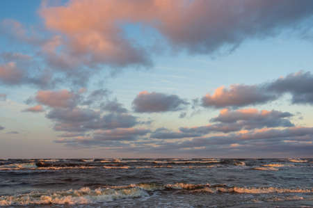 Pink clouds in the blue sky over the wavy water of the Baltic sea in the warm evening sunlight.