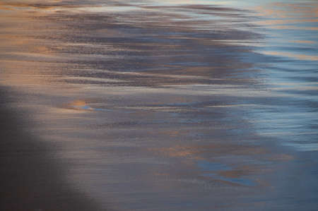 Abstract image of  reflection of sunset sky on wet seaside sand