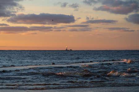 View to the Daugava river falling into the Baltic sea. Colorful sunset sky.  Daugavgriva lighthouse on the horizon.