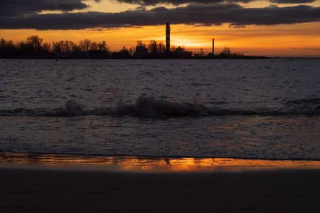 View to the Daugavgriva lighthouse from Mangalsala pier against colorful sunset sky Banco de Imagens