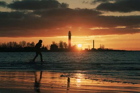 Silhouette of unrecognizable person walking on Mangalsala pier through the waves in sunset. Orange sky and silhouettes of lighthouse and port in the background