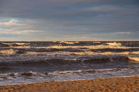 Wavy water of the Baltic sea and sandy shore in the warm evening sunlight