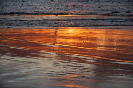 Shoreline of the sea with orange reflection of sunset sky